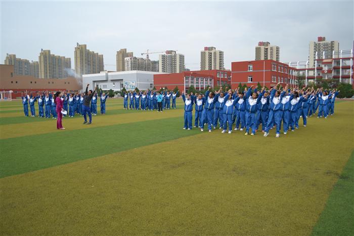 鲜花簇拥着轻盈的脚步,花香弥漫着青春的运动场。在这秋高气爽、鸟语花香的日子里,我们迎来了期待已久的唐徕回中第三十二届田径运动会。在4个校区近8000人参与的运动会开幕式上,由南校区100名女同学组成的花束队尤其为人们所关注。 运动会筹划前期,唐中南校区光荣地接受了学校总部下达的组建花束队的任务。南校区德育处精心挑选了100名女同学组成花束队并由具备舞蹈特长的郭瑞娜老师担任指导和排练任务。 在训练中,她们顶着烈日,全心全意的训练,有的同学在艰苦的训练中脚上磨出了好几个水泡,仍然没有退缩,忍着剧痛在运动场上一